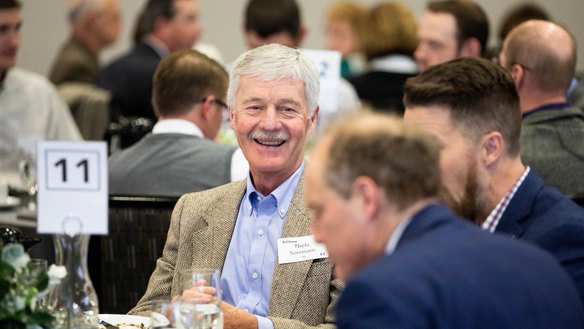 Man smiles at an event with alumni.