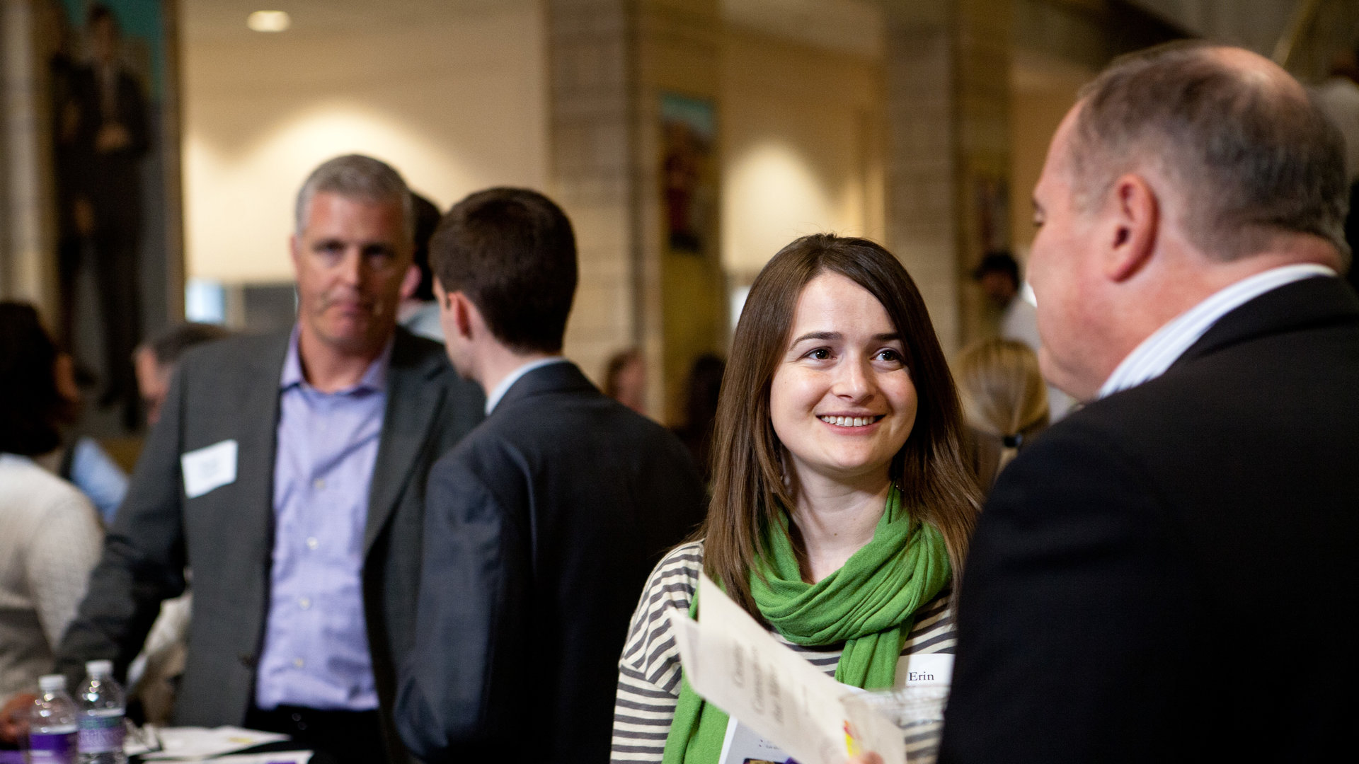 a woman speaking with a man at a st. thomas networking event