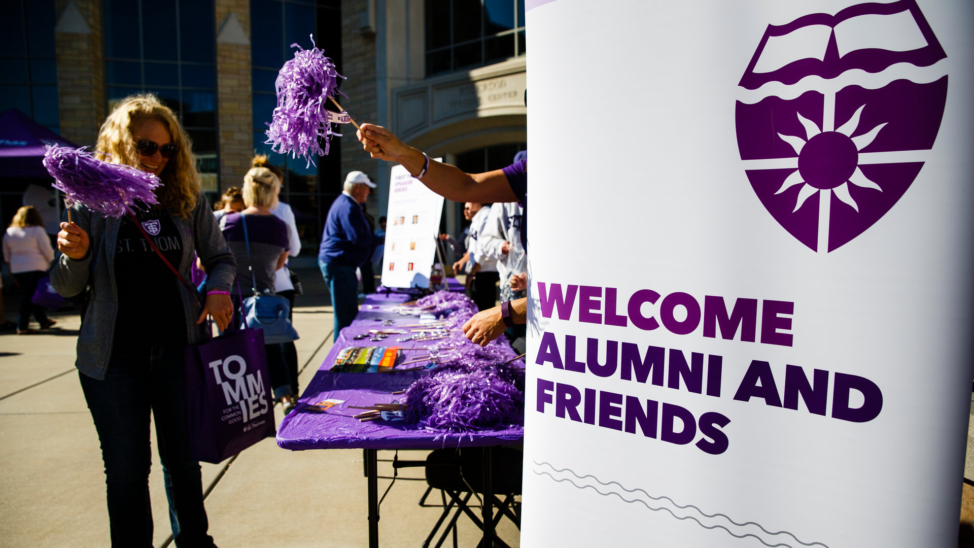 people stand by a welcome sign during an alumni event
