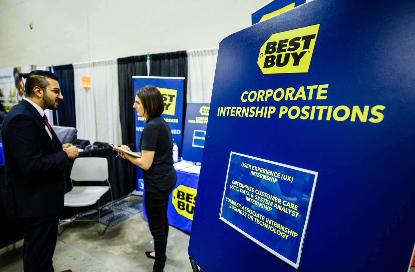 man and woman talking at a Best Buy booth at a job fair