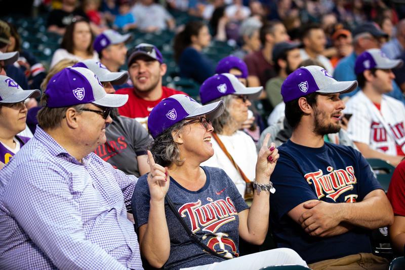 Alumni attend a Twins game and wear St. Thomas hats