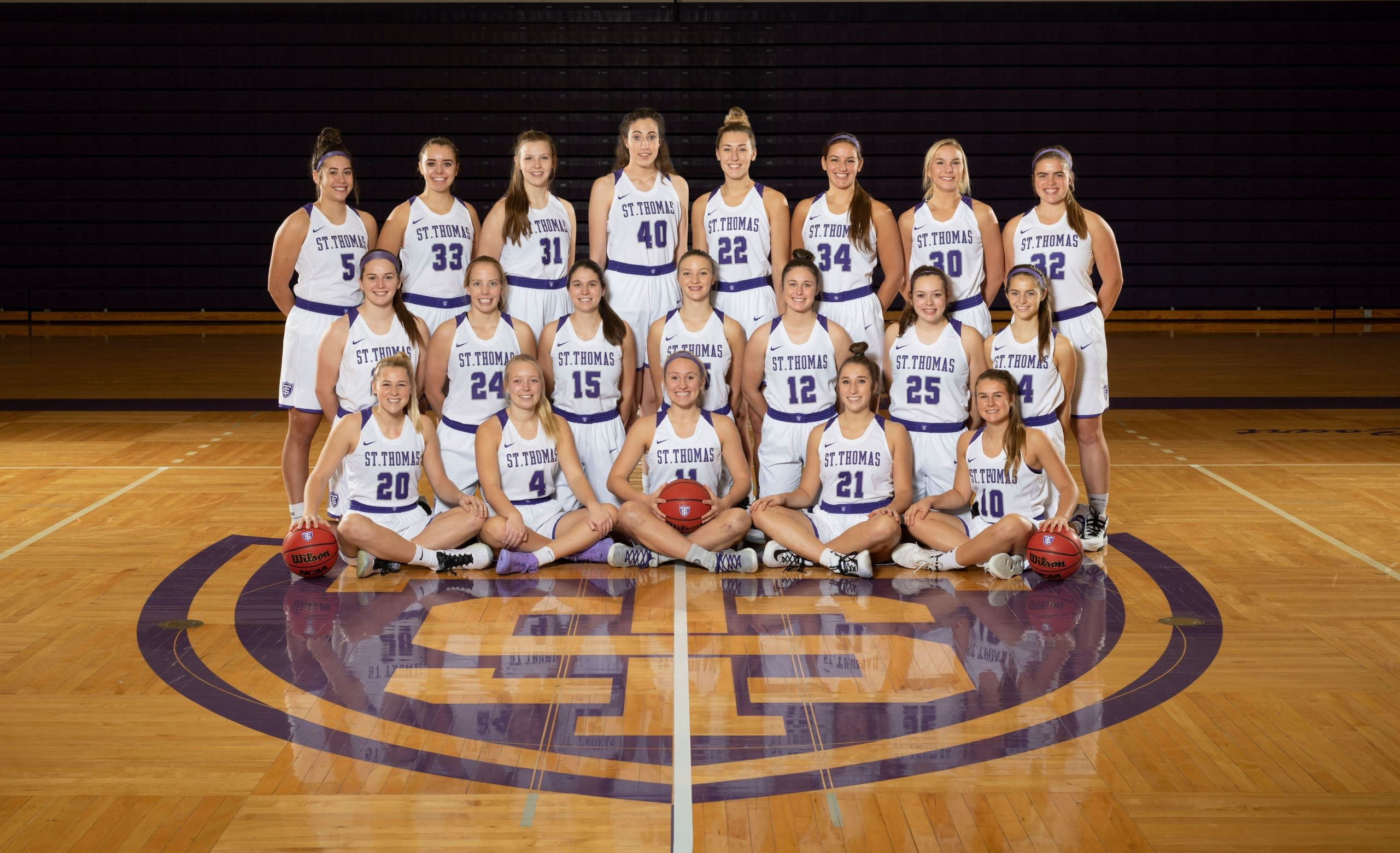 the St. Thomas Women's Basketball team poses for a photo together
