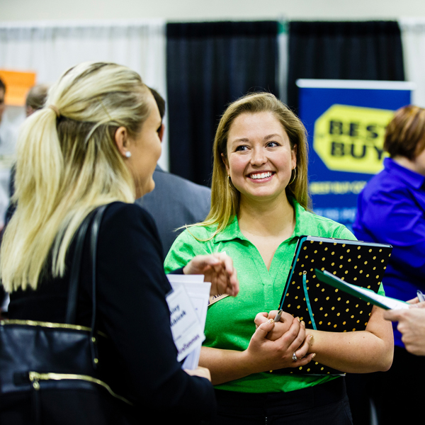 two women talking at a job fair with best buy logo in background