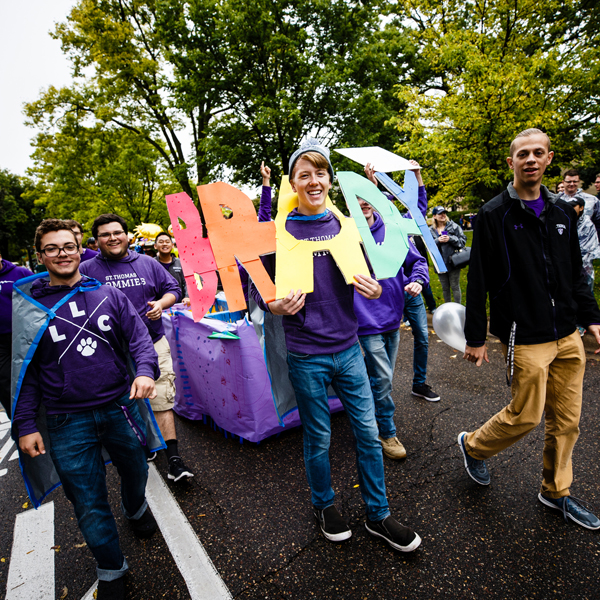 students walking in homecoming parade on summit avenue wearing a brady hall sign
