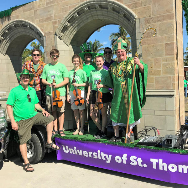 st. thomas students and faculty on a parade float with the arches in Naples, Florida