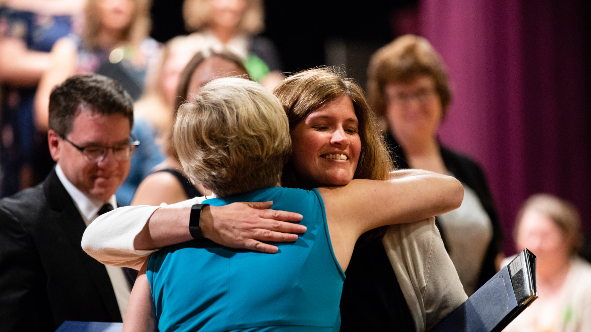 two women hugging at a reunion event