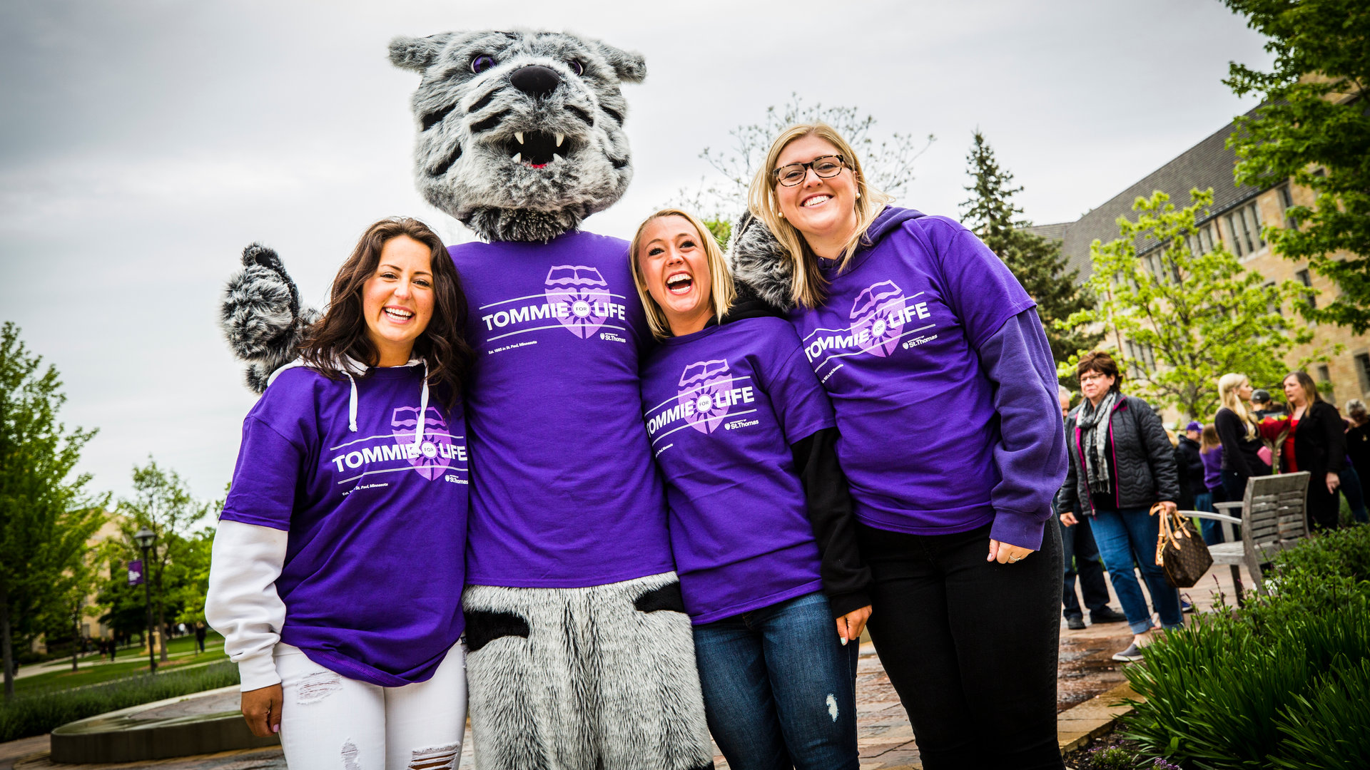 Tommie poses with alumni wearing Tommies For Life t-shirts