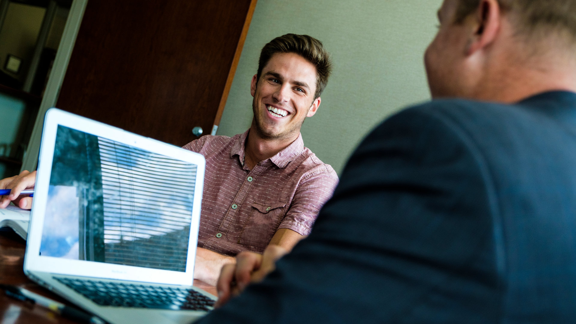 Student smiles while mentor looks at computer