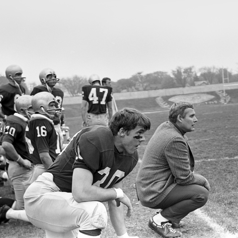 a football player stands at-the-ready next to the coach during this 1969 game