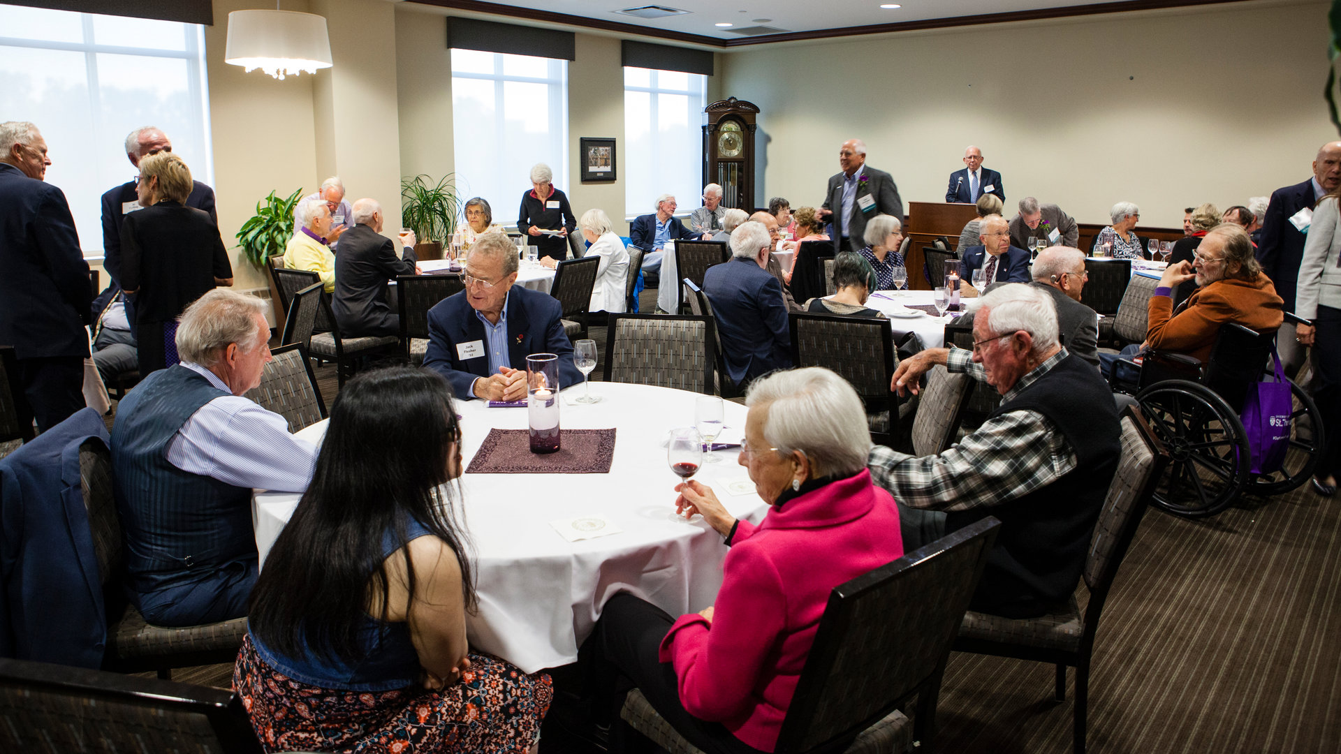 groups of Tommies chat at tables during a reunion