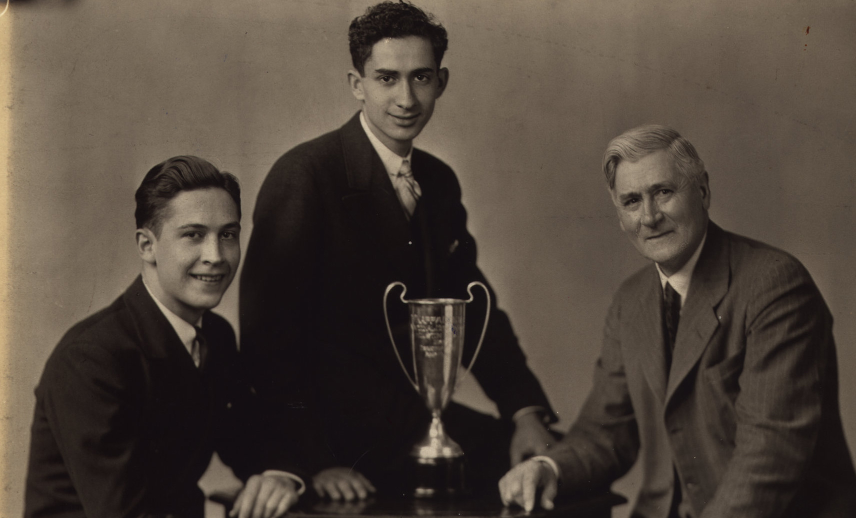 Hon. Robert Sheran (left) was the first recipient of the Distinguished Alumni award. He was on the team that won the Northwest Debate Tournament of 1936, for the College of St. Thomas.  He is shown with Abraham Kaplan and their advisor, Professor Owen McElmeel, and the winner's trophy.