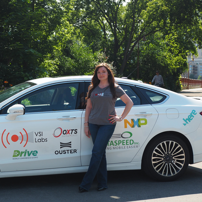 Sara Sargent '17 stands in front of a self-driving car