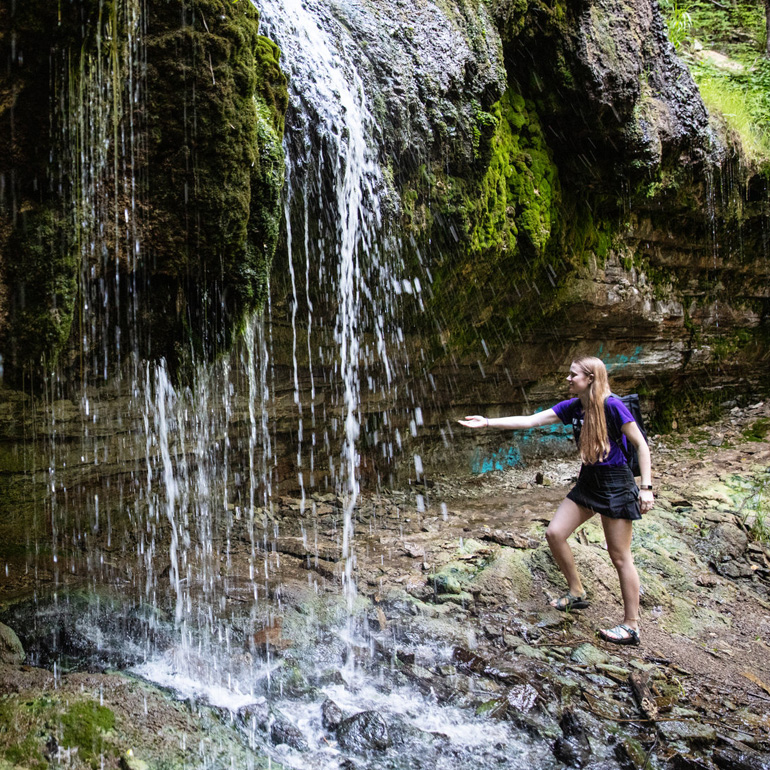 a student holds her hand out to touch the waterfall in Shadow Falls Park