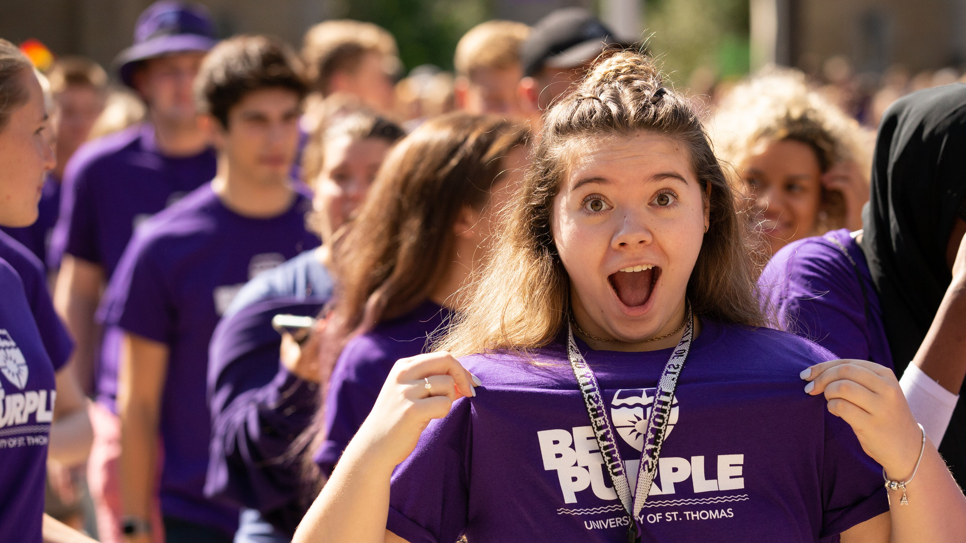 "a student holds up their ""Be Purple"" t-shirt to the crowd during the March Through the Arches event"