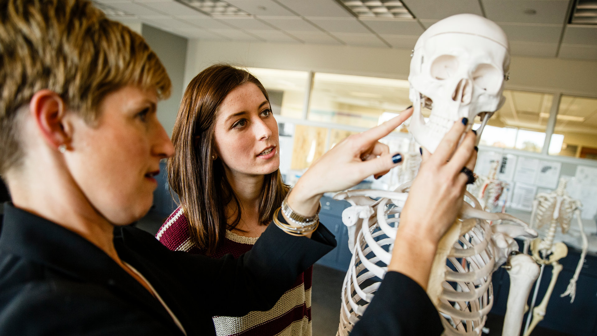 a student and her mentor observe a skeleton in a science lab