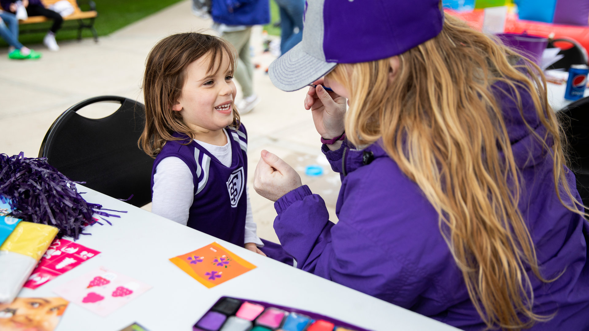 a volunteer paints a child's face during Homecoming