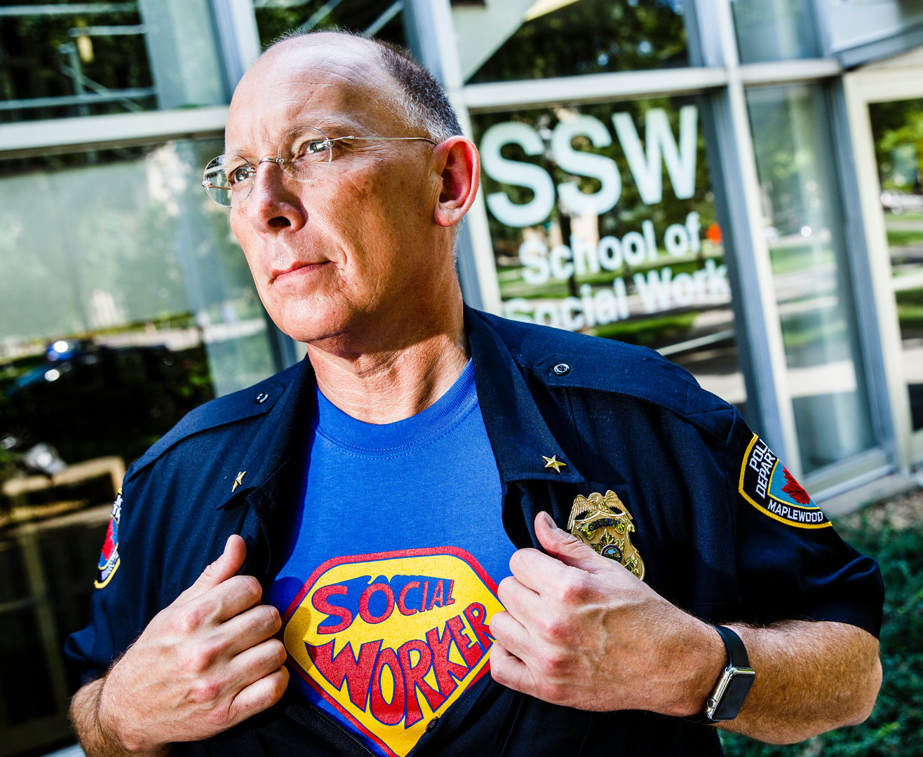 man holding uniform with superman t-shirt underneath