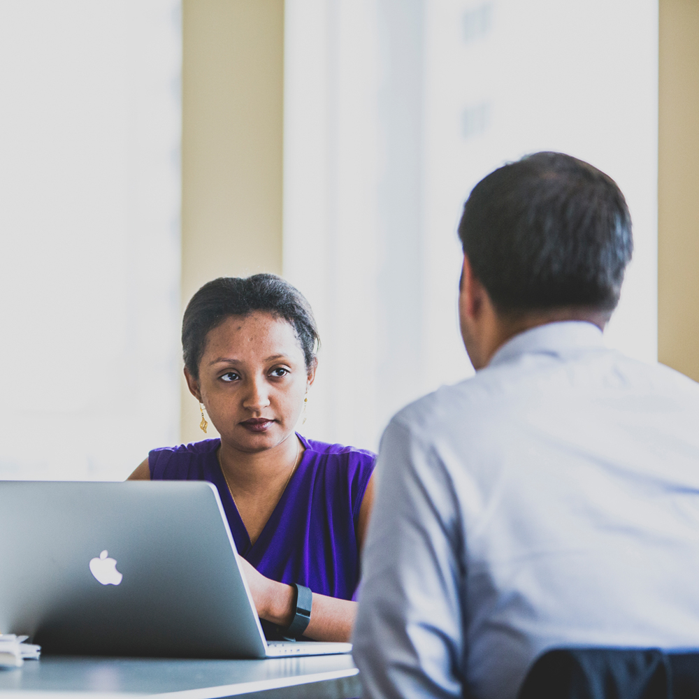 woman with apple laptop listening to a man in a conference room