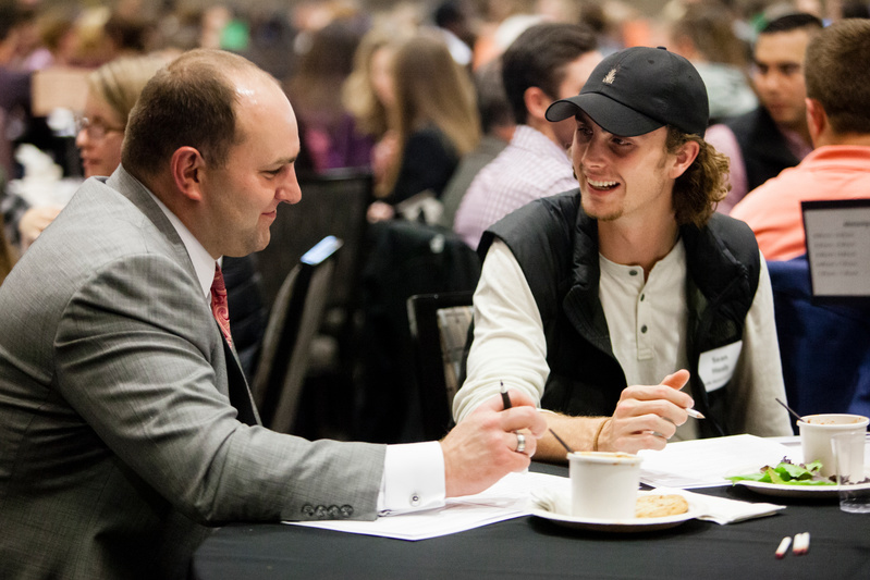 man wearing gray suit speaking with a student at a mentorship event