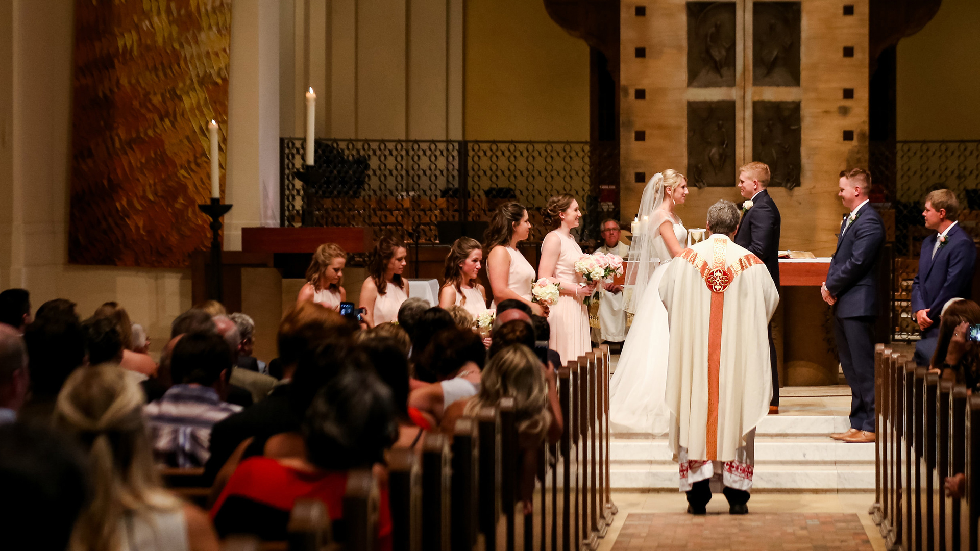 a couple stands at the altar while the priest marries them