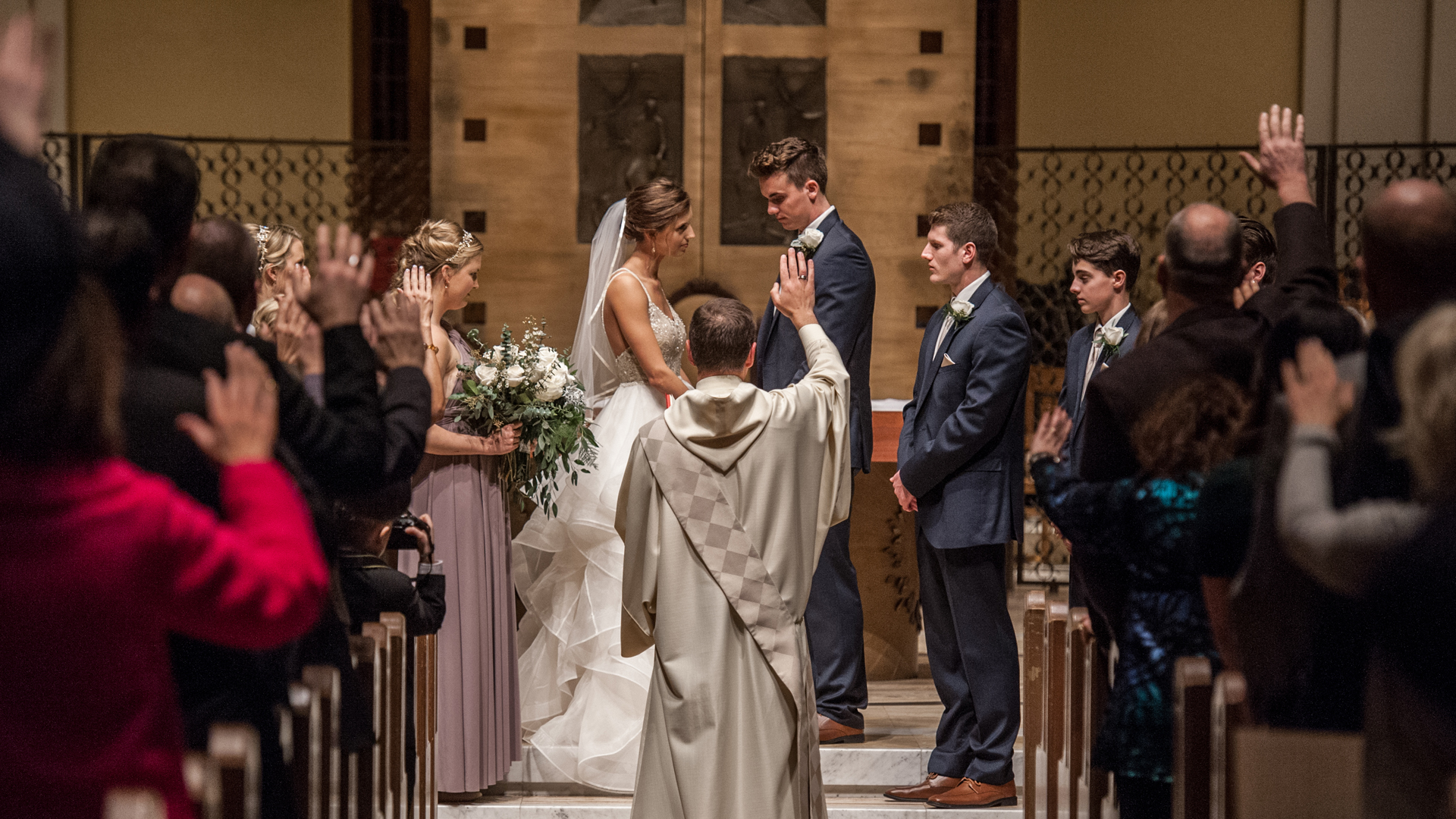a couple stands at the altar while their priest marries them